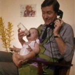 Father and baby multitasking